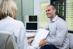 Female optometrist talking to male patient stock photo