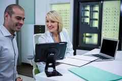 Female optometrist talking to male patient. In ophthalmology clinic Royalty Free Stock Photography
