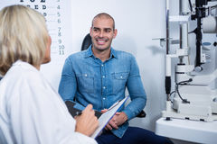 Female optometrist talking to male patient Royalty Free Stock Photography