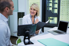 Female optometrist talking to male patient. In ophthalmology clinic Stock Image