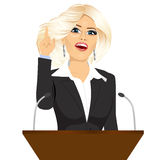 Female orator standing behind a podium with microphones Stock Photos