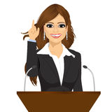 Female orator standing behind a podium with microphones Royalty Free Stock Image