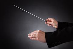 Female orchestra conductor with baton. Close-up Of Female Orchestra Conductor Holding Baton Over Black Background Stock Image