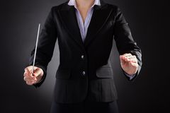 Female orchestra conductor with baton. Close-up Of Female Orchestra Conductor Holding Baton Over Black Background Royalty Free Stock Photos