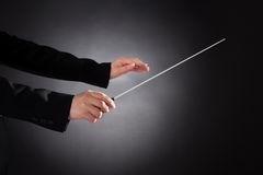 Female orchestra conductor with baton. Close-up Of Female Orchestra Conductor Holding Baton Over Black Background Royalty Free Stock Photo
