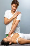Female osteopath manipulating arm on patient. Close up of female physiotherapist doing arm and shoulder treatment on patient royalty free stock images