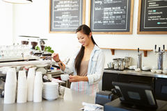 Female Owner Of Coffee Shop. Making a Coffee stock image
