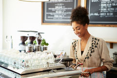 Female Owner Of Coffee Shop. Making Coffee stock photos