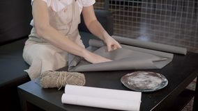 Craft ceramist woman is wrapping exclusive handmade ceramic plates in paper. Female packers is packing handmade tableware in grey wrapping paper. Woman is stock footage