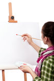 Female painter. Beautiful girl with brushes near easel, painting on canvas Royalty Free Stock Photography