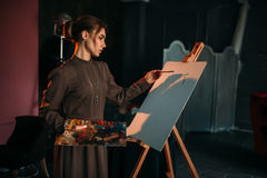 Female painter with brush and palette in hands. In art studio. Oil paint, paintbrush drawing Stock Photo
