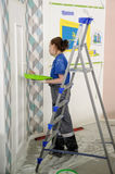 Female painter decorates wall, performing task Royalty Free Stock Photo
