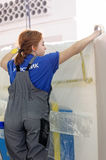Female painter decorates wall, performing task Royalty Free Stock Photos