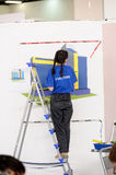 Female painter decorates wall, performing task Royalty Free Stock Images