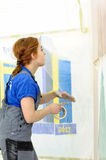 Female painter decorates wall, performing task Stock Image