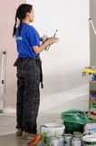 Female painter decorates wall, performing task Royalty Free Stock Image