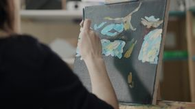 Woman artist is highly artistic turning a brush with paint over canvas in studio. Female painter is drawing in her workshop, touching canvas by brush with dye stock video
