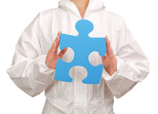 Female painter holding a blue puzzle piece Stock Photo