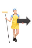 Female painter holding a paint roller and an arrow Stock Photo