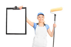 Female painter holding paint roller and a clipboard Royalty Free Stock Images