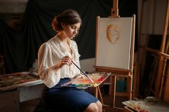 Female painter holds color palette and brush stock photo