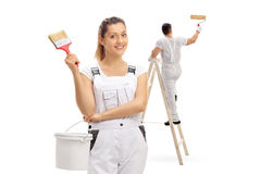 Female painter with male painter painting climbed up a ladder Stock Photos