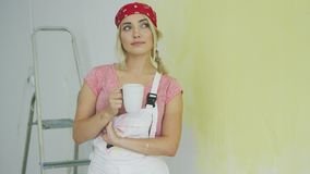Female painter in overalls resting with drink stock video