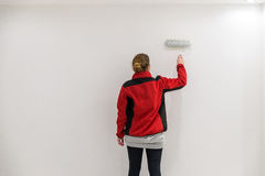 Female painter with paint roller in front of wall as template Royalty Free Stock Photo