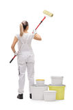 Female painter painting with a paint roller Royalty Free Stock Images