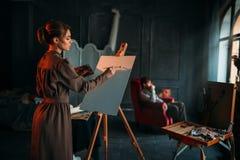 Female painter paints man portrait in art studio Royalty Free Stock Photo