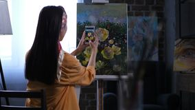 Female painter photographing artwork with peonies. Back view of woman artist taking photo of finished masterpiece on smartphone in home art studio. Female stock video footage