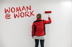 Female painter with red paint roller in front of wall as templat Royalty Free Stock Photography