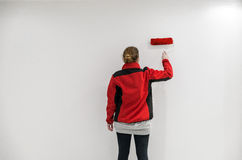 Female painter with red paint roller in front of wall as templat Royalty Free Stock Photo