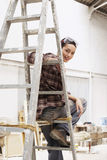 Female Painter Sitting On Ladder In Work Site Royalty Free Stock Photography