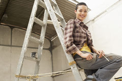 Female Painter Sitting On Ladder At Work Site. Portrait of happy young female painter sitting on ladder at work site royalty free stock images