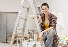 Female Painter Sitting On Ladder At Work Site. Portrait of happy young female painter sitting on ladder at work site stock images