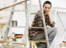Female Painter Sitting On Ladder In Work Site. Portrait of young female painter sitting on ladder in work site royalty free stock photo