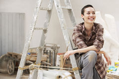 Female Painter Sitting On Ladder At Work Site Stock Photos