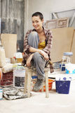 Female Painter Sitting On Stool In Work Site. Portrait of young female painter sitting on stool in work site royalty free stock image