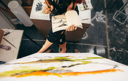 Female painter sitting in studio making a drawing. Top view of female painter sitting in studio making a drawing in her book. Cropped shot woman artist painting Stock Images
