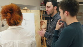 Female painter teaching young men how to draw classical portrait stock video footage