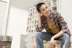 Female Painter On Work Break In Tool Room Royalty Free Stock Photos