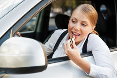 Female painting her lips and driving the car Stock Image