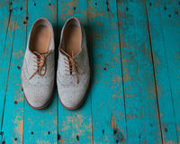 Female pair of suede light shade shoes on the wooded background Stock Photos