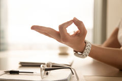 Female palm with fingers folded in Jnana mudra gesture. From eastern spiritual practices. Businesswoman relaxing at the table in office. Meditating at workplace Stock Photos