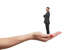 Female palm holding small happy businessman. Big caucasian female palm holding small happy businessman. isolated on white background stock images