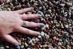 Female palm on the pebble. Woman hand on the coloured beach pebble background stock images
