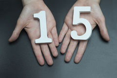On the female palms figure fifteen. On black background female hands with number fifteen Stock Photos