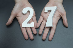 On the female palms figure twenty-seven. On a black background, female hand with number twenty-seven Royalty Free Stock Photos