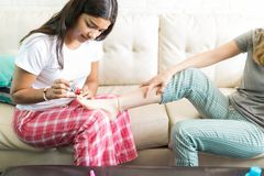 Female Pampering Friend By Applying Nailpolish On Couch. Female enjoying sleepover and pampering friend by applying nailpolish on couch at home stock image